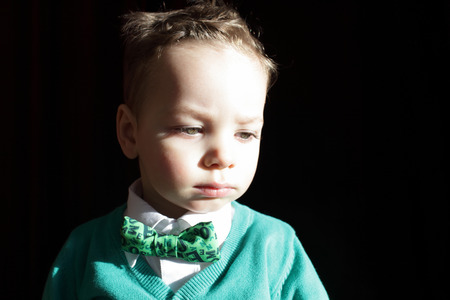 hair tie: Kid in a green cardigan with white shirt and bow tie