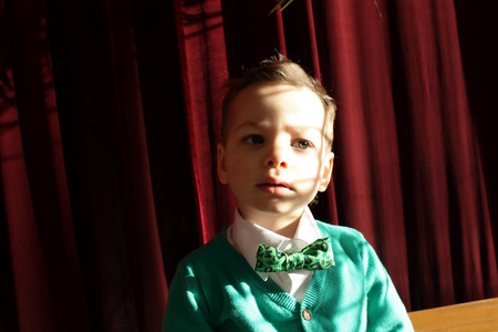 noeud papillon: Kid in green cardigan on the red curtain  Banque d'images