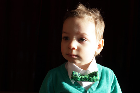 hair tie: Serious child in green cardigan with white shirt Stock Photo