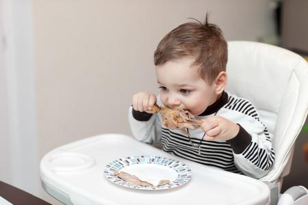 highchair: Boy eating a duck leg in a highchair Stock Photo