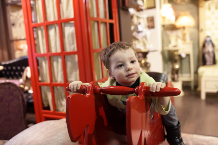 Child sitting on a red rocking horse at home photo