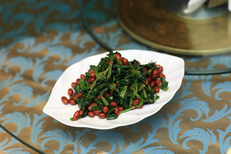 chinese spinach: Appetizer of wilted spinach with peanuts in a chinese restaurant Stock Photo