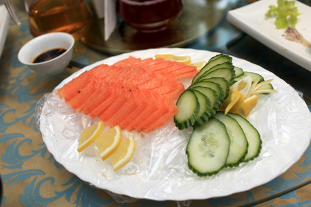 Salmon sashimi with lemon and cucumber at a chinese restaurant photo