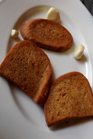 Toasts with garlic on a white plate in the restaurant photo
