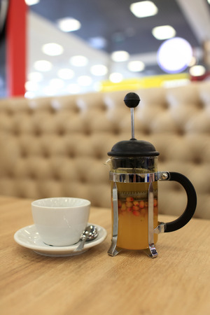 Buckthorn tea in a french press on a table in the cafe photo