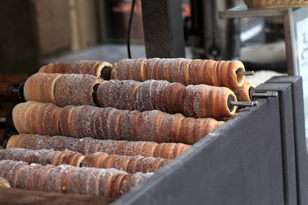 Baking of czech trdelnik on the street of Prague photo