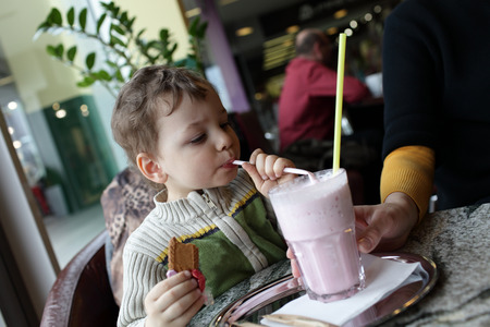 Child drinks milk strawberry smoothie in the cafe photo