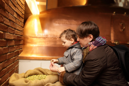 Mother and her son touching hop in the old brewery photo