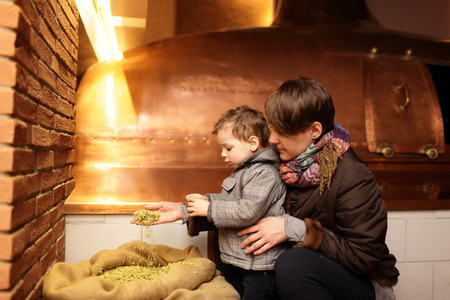 Mother shows her son hop in the old brewery photo
