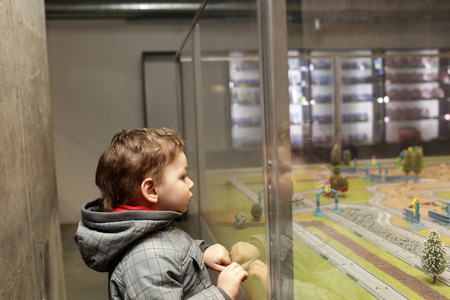 Child looking at toy city in the indoor playground photo