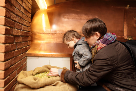 Mother with her son touching hop in the museum of brewery photo