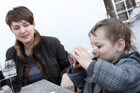 Mother with her son have beverages in the cafe photo