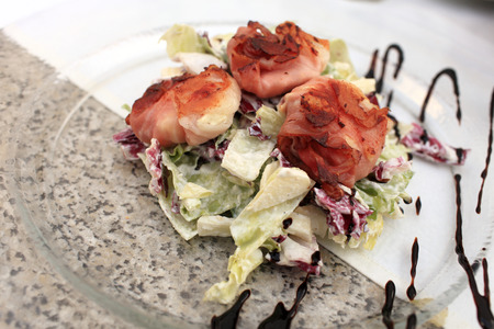 Fried goat cheese in bacon with salad on glass plate in the czech restaurant photo