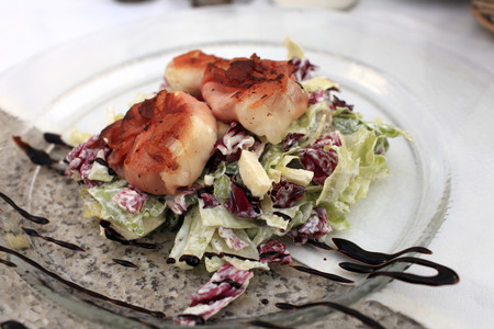 Fried goat cheese in bacon on salad in the czech restaurant photo