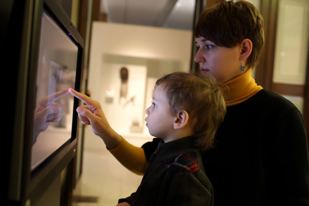 Mother and her son using touch screen in a museum photo