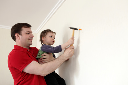 Family installing plastic anchor into wall at home photo