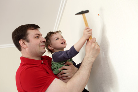 Father with his son installing plastic anchor into wall photo