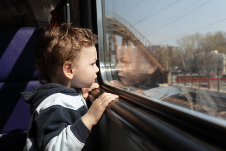 Child looks through the window of the train photo