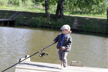 piedi nudi ragazzo: Un ragazzo a piedi nudi di pesca in uno stagno