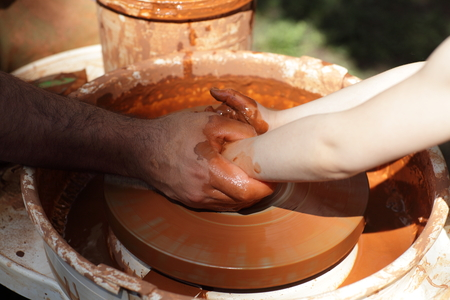 Learning pottery on a wheel in outdoor photo