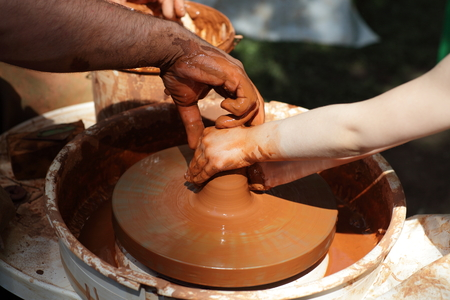 Hands of potters on a wheel in the classroom photo