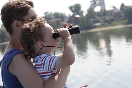 Boy looking through binoculars on Volga river photo