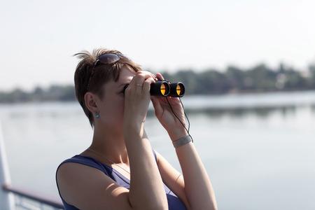 The girl looking around through binoculars on Volga river photo