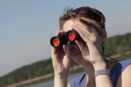 Girl looking through binoculars on Volga river photo