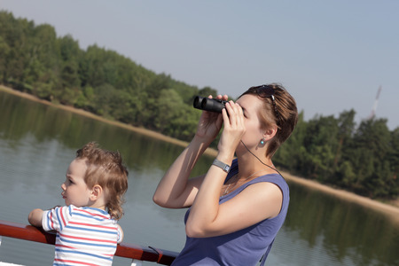 Mother looking through binoculars on Volga river photo