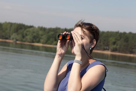 The woman looking around through binoculars on Volga river photo