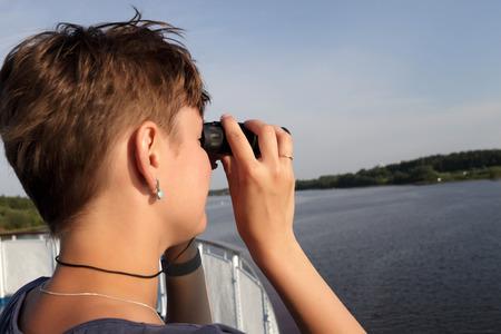 Woman looking through binoculars on Volga river photo