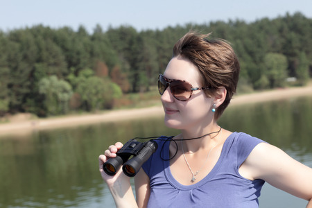 Portrait of a woman with binoculars on a Volga river background photo