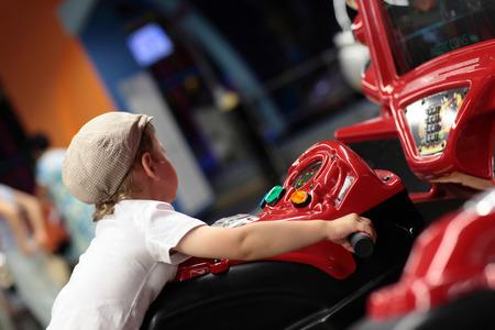 Kid playing arcade simulator machine at an amusement park photo