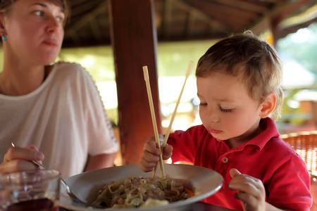 familia cenando: La familia comiendo fideos en un restaurante asi�tico