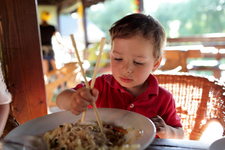 eating noodles: The boy eating noodles in an asian restaurant