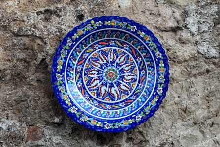 The floral decorative plate on a wall background photo