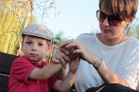 lavamanos: Madre limpia las manos a su hijo en el parque Foto de archivo