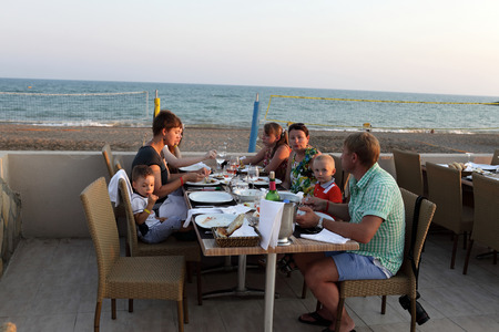 Family has dinner in the beach restaurant at sunset photo