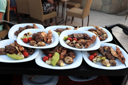 Grilled meat and vegetables on the white plates photo