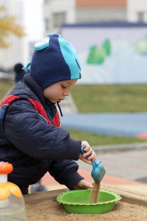Boy playing in sandbox at playground in spring photo