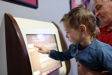 Family using touch screen in the museum photo