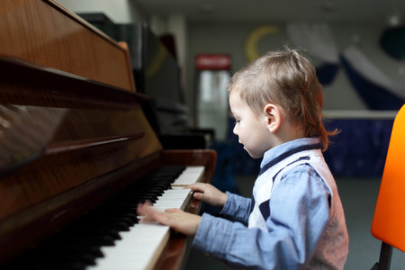 prodigy: Kid playing the piano at a classroom