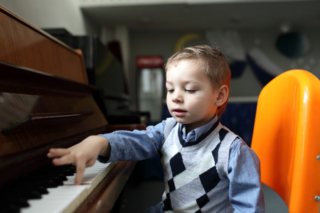 prodigy: Child learning to play the piano at a classroom Stock Photo