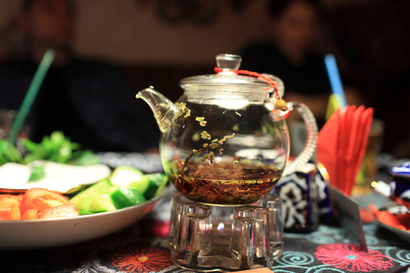 uzbek: The glass teapot on a table in the asian restaurant Stock Photo