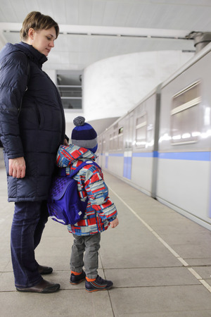 subway platform: Mother with her son waiting train on subway platform