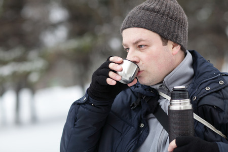 winterly: Man has hot tea in the winter park