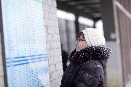 Senior woman looks at train schedule at the station photo