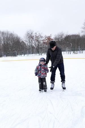 ni�o en patines: Abuelo con el nieto jugar en la pista de patinaje