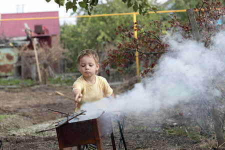 3 persons only: Boy making fire in a grill at the backyard Stock Photo