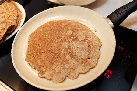 flaxseed: Pan with flaxseed meal pancake on a stove at home Stock Photo